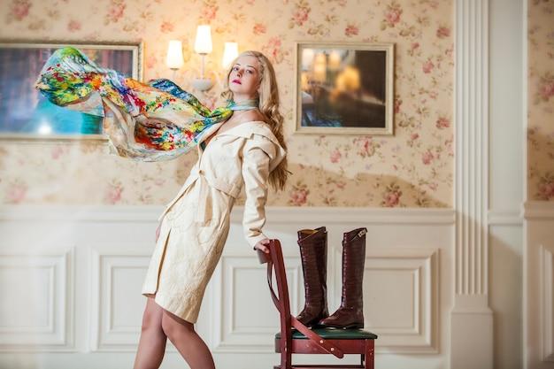 Modello femminile in cappotto luminoso con una sciarpa volante e labbra rosa brillante in un interno vintage