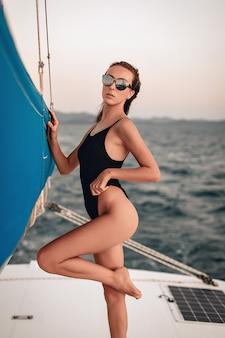 Modello femminile che indossa un body nero e occhiali da sole e posa su uno yacht bianco, sollevando la gamba in una posa sexy.