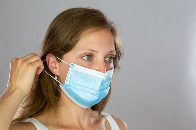Modello femminile in camicia bianca che attacca la mascherina chirurgica