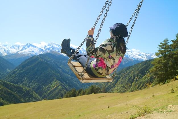 Femmina sull'altalena di montagna con vista mozzafiato sulla montagna del caucaso nella città di mestia in georgia