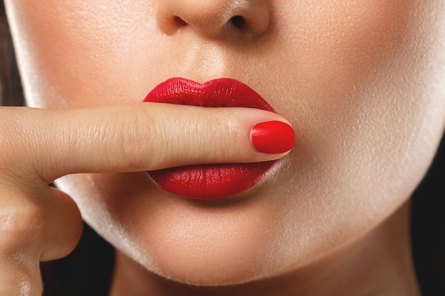 Bocca e unghie femminili con il manicure e il rossetto rossi.