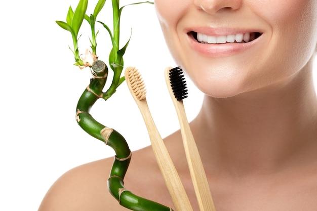 Bocca femminile con denti bianchi e spazzolino da denti di bambù
