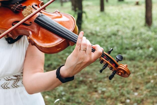 Musicista femmina si esibisce a un matrimonio all'aperto.