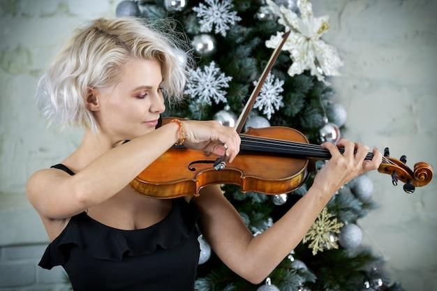 Il violinista musicista femminile suona il violino sull'albero di natale sullo sfondo