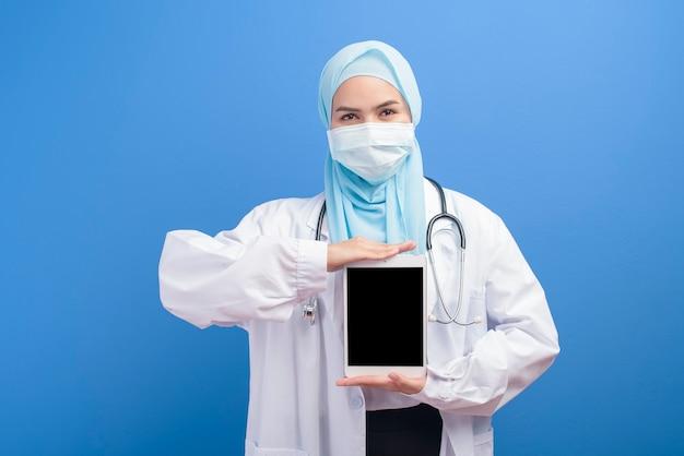 Un medico musulmano femminile con l'hijab che indossa una mascherina chirurgica facendo uso della compressa sopra l'azzurro