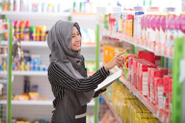 Commerciante musulmano femminile che lavora al supermercato