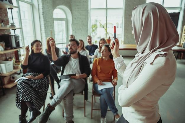 Altoparlante musulmano femminile che dà presentazione in sala al workshop. udienza o sala conferenze. chiedere ai partecipanti in udienza. evento congressuale, formazione. istruzione, diversità, concetto inclusivo.