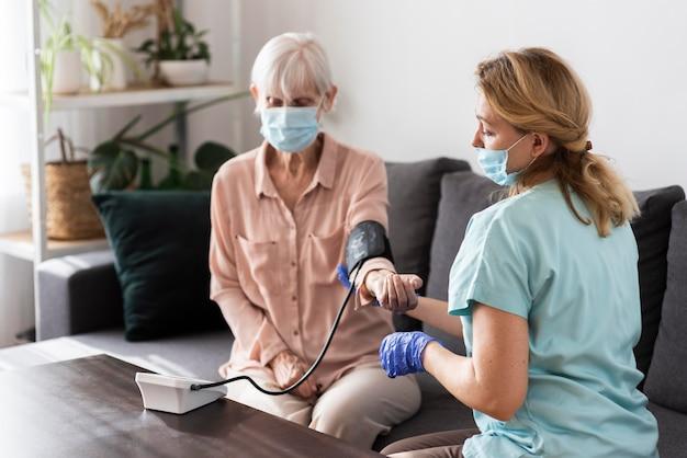 Infermiera femminile con mascherina medica utilizzando un monitor della pressione sanguigna sulla donna anziana