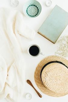 Scrivania da ufficio femminile con caffè, libro, cappello di paglia, fiori e coperta su superficie bianca