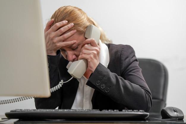 La responsabile dell'ufficio femminile è sotto stress davanti a un laptop che risponde alle chiamate dei clienti