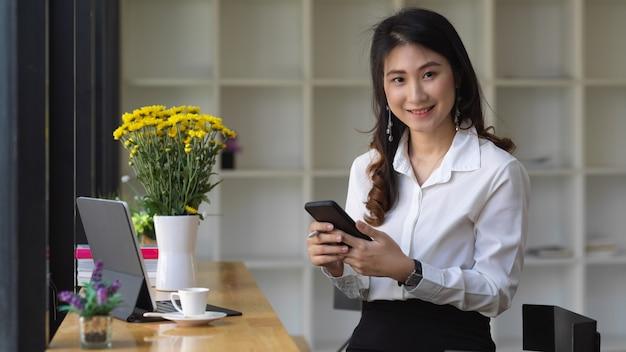 Impiegato femminile che tiene il suo smartphone