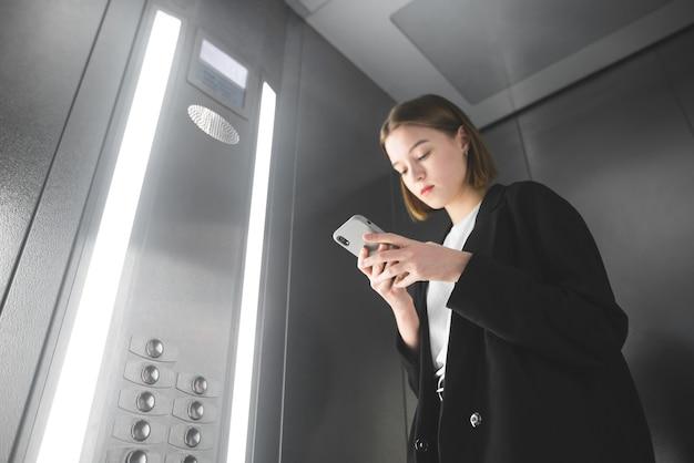 Impiegata femminile sta guardando lo schermo del suo smartphone in ascensore.