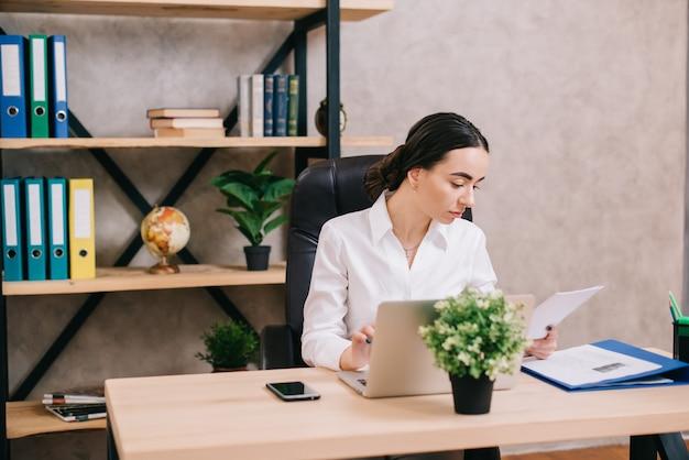 Impiegata femminile che visualizza documenti sul posto di lavoro