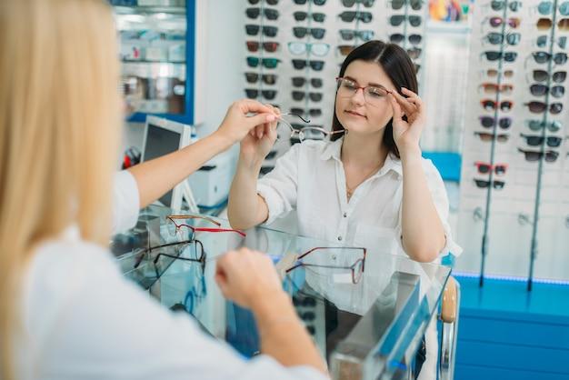 Ottico e consumatore femminile sceglie la montatura degli occhiali nel negozio di ottica. selezione di occhiali con un optometrista professionista