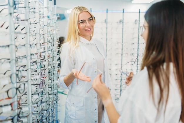 L'ottico femminile e il cliente spara gli occhiali nel negozio di ottica. selezione di occhiali da vista con un optometrista professionista.