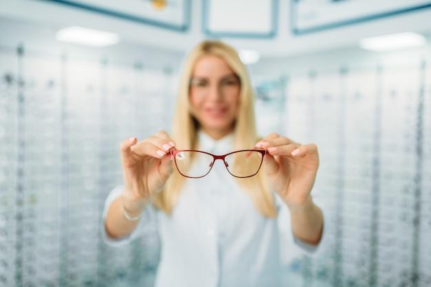 L'ottico femminile mostra gli occhiali nel negozio di ottica. selezione di occhiali da vista con un optometrista professionista