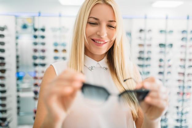 L'ottico femminile mostra gli occhiali da sole nel negozio di ottica. selezione di protezione per gli occhi con optometrista professionista, concetto di optometria
