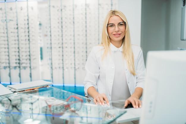 Ottico femminile seduto al tavolo, vetrina con occhiali nel negozio di ottica.