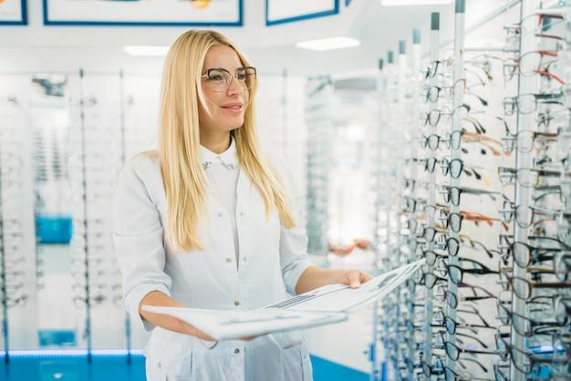 Ottico femminile con catalogo di occhiali nelle mani in piedi contro la vetrina con occhiali nel negozio di ottica.