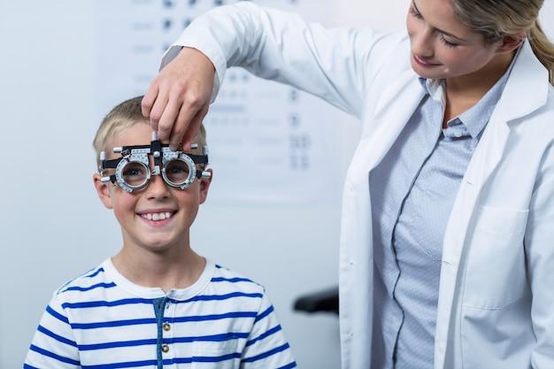Optometrista femmina che esamina giovane paziente con phoropter
