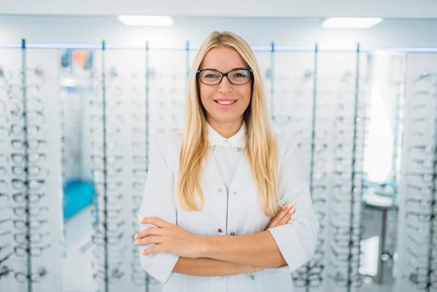 All'ottico optometrista femmina in piedi contro la vetrina con gli occhiali nel negozio di ottica. selezione di occhiali da vista con ottico professionista