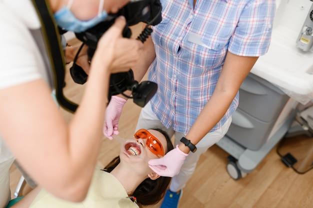 Ortodontista femminile, assistente e paziente in clinica, stomatologia
