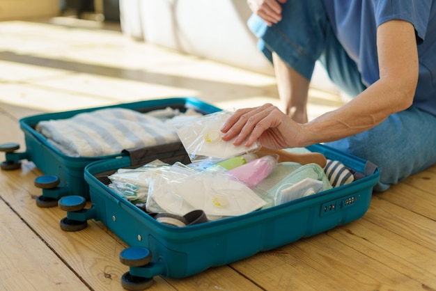 Imballaggio femminile che tiene il respiratore mentre si prepara la valigia per il viaggio durante l'epidemia di covod