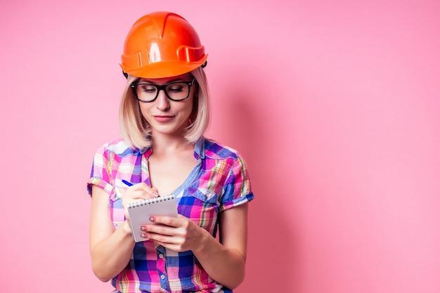 Pittore femminile che utilizza il rullo per rinnovare il colore della parete rosa al chiuso. donna sorridente in camicia a scacchi di affari che indossa il casco del costruttore che dipinge le pareti dell'appartamento.