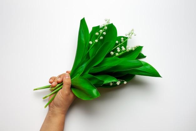 La palma femminile tiene un bouquet di mughetto sullo sfondo bianco isolato estate o madri da...