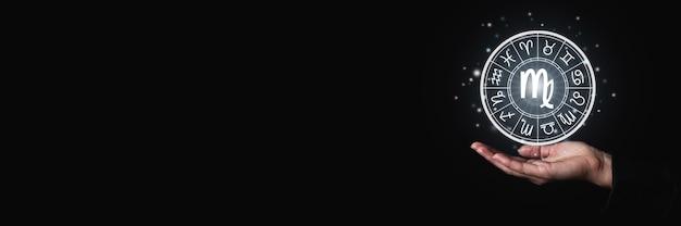 Il palmo femminile tiene un segno luminoso con i simboli dei segni zodiacali nell'oscurità. bandiera.