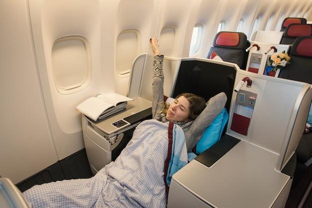 Passeggero femminile rilassante presso la business class dell'aeroplano in comodo sedile unico