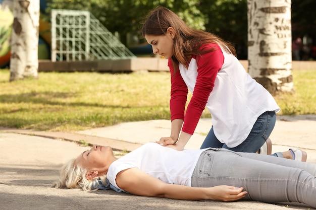 Passante femminile che esegue la rcp su una donna matura priva di sensi all'aperto