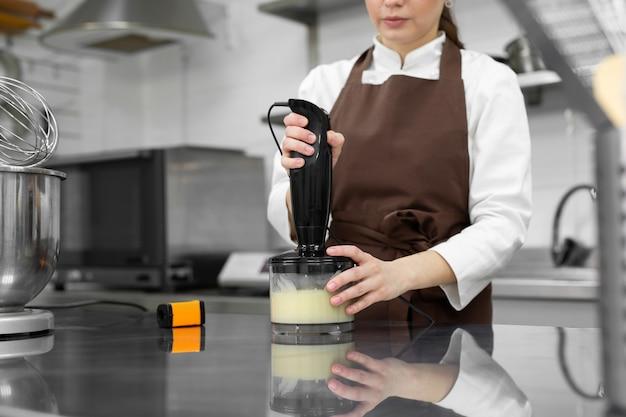 Il pasticcere femminile prepara una glassa a specchio per una torta, la frusta in un frullatore.