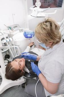 Paziente di sesso femminile che ottiene il trattamento dentale dal dentista esperto