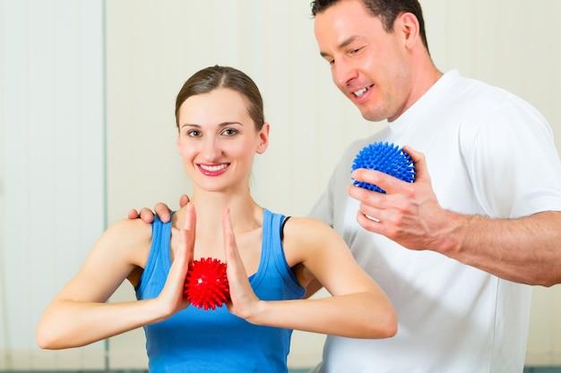 Paziente di sesso femminile in fisioterapia facendo esercizi fisici con il suo terapista, usando una palla da massaggio