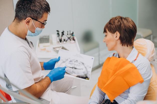 Paziente di sesso femminile in visita dal dentista nemico denti igiene