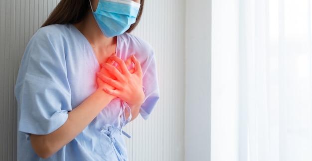 Paziente di sesso femminile che indossa una maschera e tiene la mano sul petto a causa di sintomi di infarto