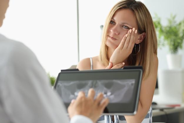 Paziente femminile con mal di denti acuto all'appuntamento medico con immagine a raggi x x