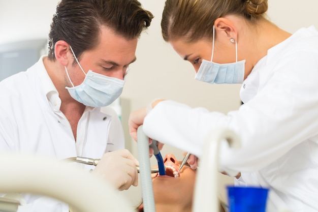 Paziente di sesso femminile con trattamento odontoiatrico dentale e assistanta, indossando maschere e guanti