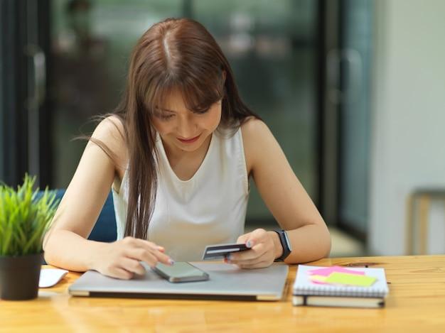 Pagamento femminile tramite carta di credito installata applicazione online per fornire transazioni di pagamento senza contanti