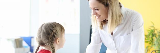 Il medico pediatra femminile comunica con la bambina. esame medico del concetto di bambini