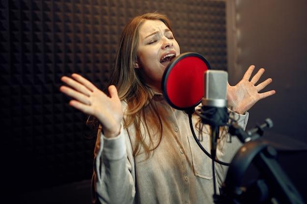 L'artista femminile in cuffia canta una canzone al microfono, all'interno dello studio di registrazione sullo sfondo. registrazione vocale professionale, posto di lavoro del musicista, processo creativo, audio moderno