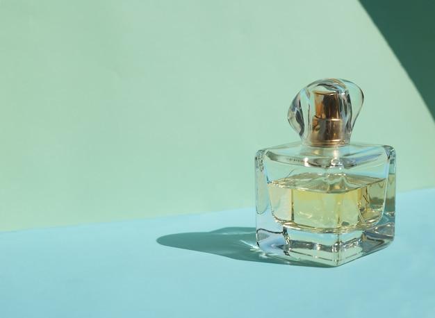 Bottiglia di profumo femminile su uno sfondo blu pastello con ombre di cristallo.