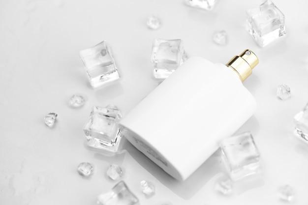 Bottiglia bianca della stuoia del profumo femminile, fotografia oggettiva della bottiglia del profumo in cubetti di ghiaccio e acqua sul tavolo bianco