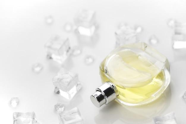 Bottiglia di profumo femminile giallo, fotografia oggettiva della bottiglia di profumo in cubetti di ghiaccio e acqua sul tavolo bianco