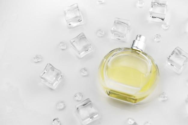 Bottiglia di profumo femminile giallo, fotografia oggettiva della bottiglia di profumo in cubetti di ghiaccio e acqua sul tavolo bianco.