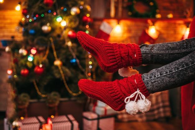 Piedi di persona di sesso femminile in calzini rossi allegri, albero di natale con decorazioni