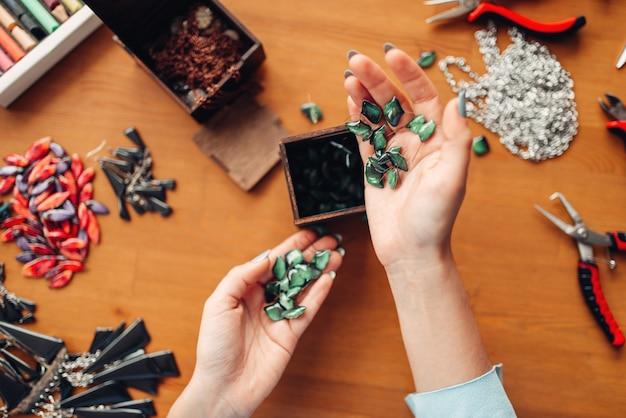 Persona di sesso femminile le mani tiene accessori di ricamo, vista dall'alto, maestro sul posto di lavoro. gioielli fatti a mano su tavola di legno, fabbricazione di bigiotteria