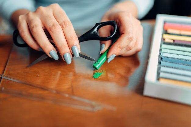 Le mani di persona femminile tiene le forbici e l'argilla polimerica verde, maestro al lavoro. gioielli fatti a mano. ricamo, bigiotteria