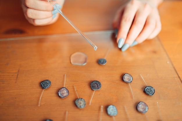 Le mani di persona di sesso femminile fanno la decorazione di moda. gioielli fatti a mano. ricamo, accessori donna